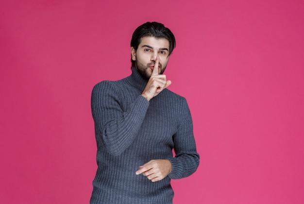 Homme à la barbe faisant signe de silence ou pointant un volume élevé.
