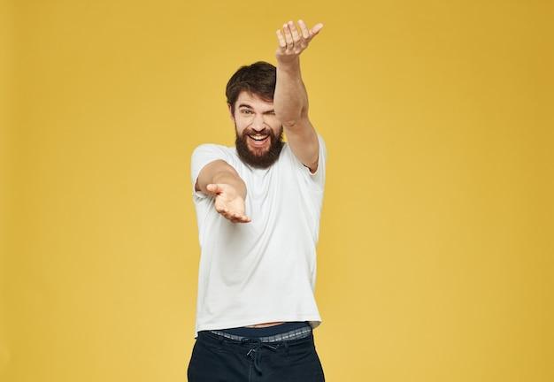 Un homme avec une barbe fait des gestes avec ses mains sur un fond jaune et un pantalon sombre est un modèle. photo de haute qualité