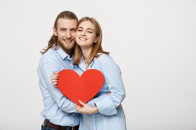 Un homme avec une barbe et une femme avec des cheveux courts blonds tenant du papier coeur rouge.