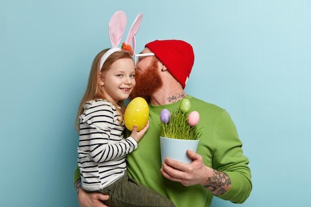 Homme à la barbe de gingembre portant des vêtements colorés et tenant sa fille