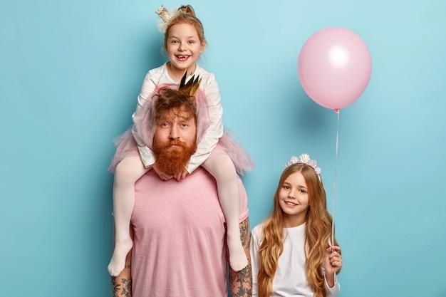Homme à la barbe de gingembre et ses filles avec des accessoires de fête