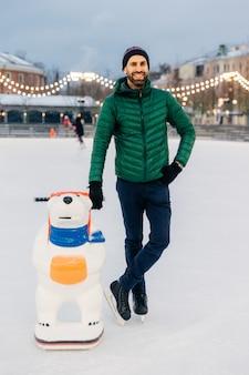 Un homme à la barbe heureuse porte une veste et un chapeau verts, se tient près de l'aide du skate pour essayer d'acquérir des compétences de patinage