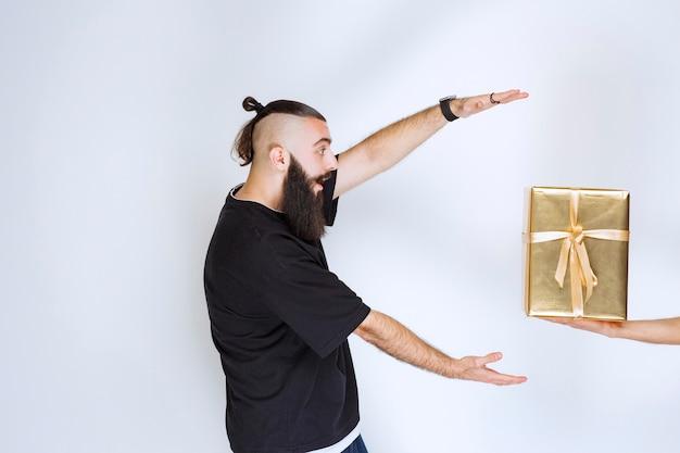 Homme à la barbe impatient de prendre un coffret cadeau doré qui lui est offert.
