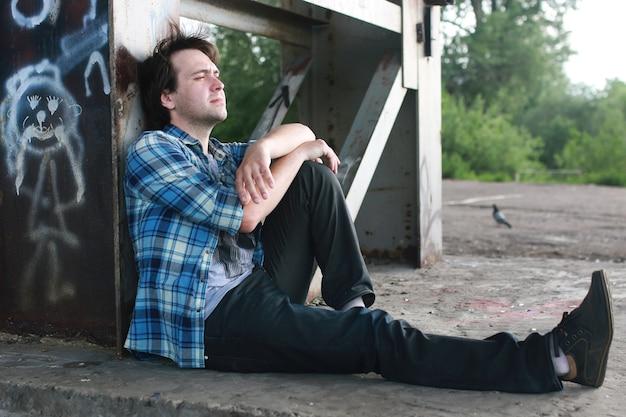 Un homme avec une barbe et un jean se tient dans la zone industrielle