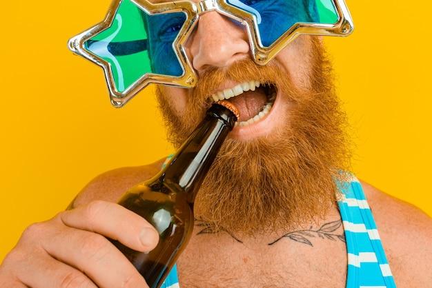 Homme avec barbe et lunettes de soleil boit de la bière