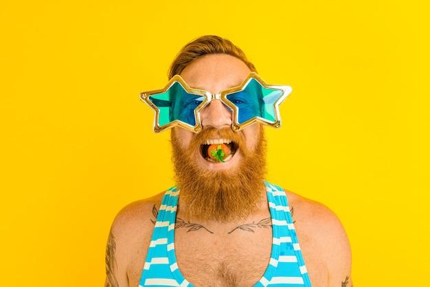 L'homme avec la barbe et les lunettes de soleil mange une fraise