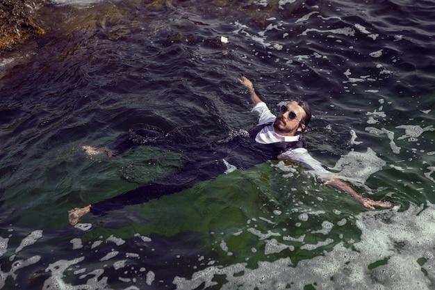 Homme avec une barbe et des lunettes de soleil en vêtements un gilet et une chemise blanche nage en mer parmi les rochers en été