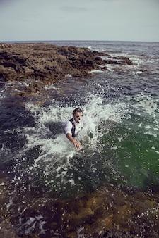 Homme avec une barbe et des lunettes de soleil en vêtements un gilet et une chemise blanche sautent en mer parmi les rochers en été
