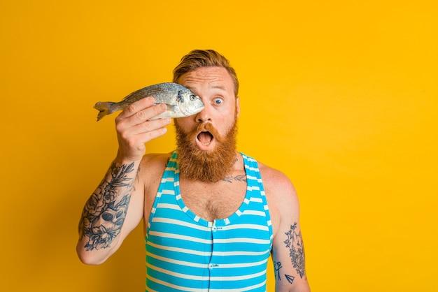 L'homme avec la barbe et le maillot de bain a attrapé un poisson