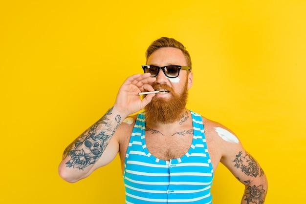 Homme avec barbe et maillot de bain fume une cigarette