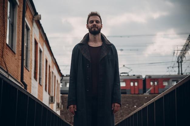 Homme avec barbe en manteau restant sur le pont contre le train