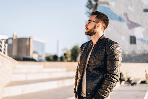 Homme à la barbe marchant en plein air dans la rue.