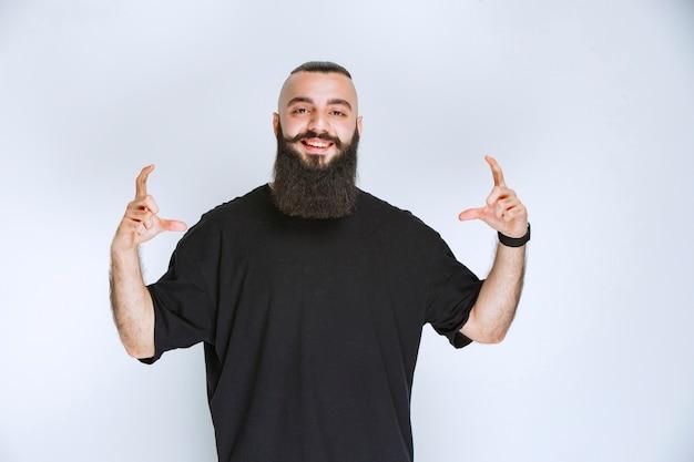 Homme à la barbe montrant les dimensions d'un objet.