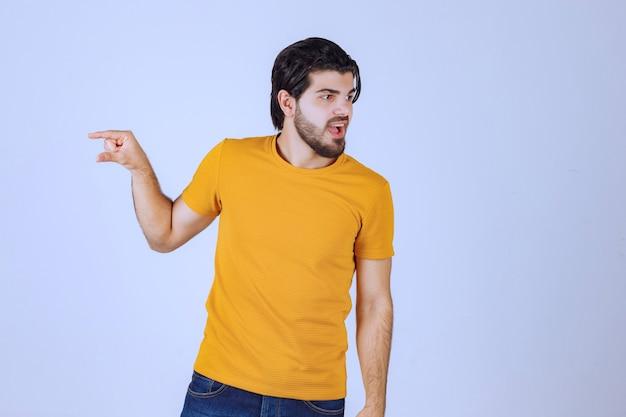 Homme à la barbe montrant les mesures estimées d'un objet