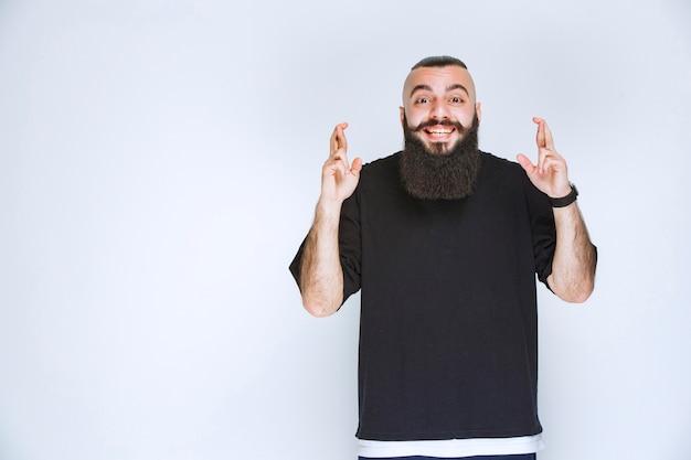 Homme à la barbe montrant un signe de croix de doigt.