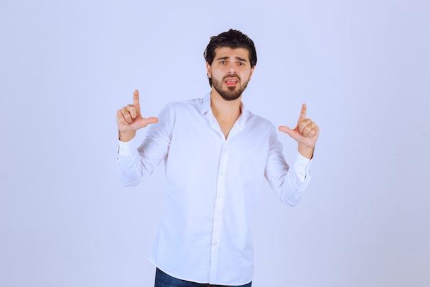 Homme à la barbe montrant le signe de la main du perdant.