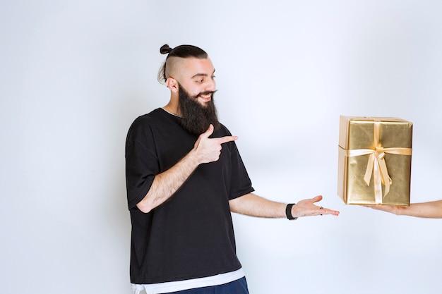 Homme à la barbe montrant son coffret cadeau doré.