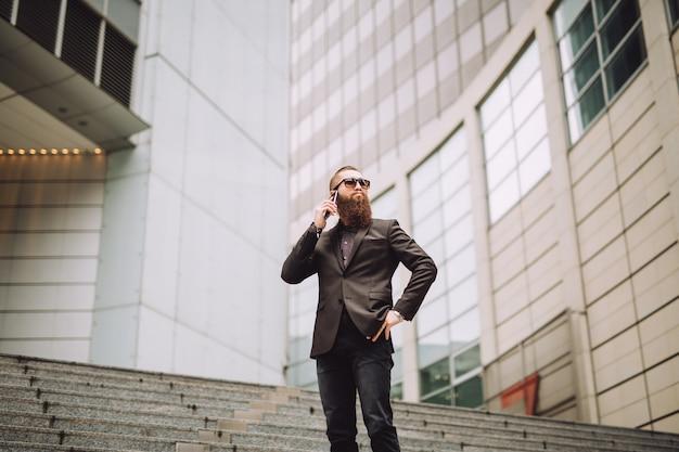 L'homme à la barbe parle au téléphone près de la banque.
