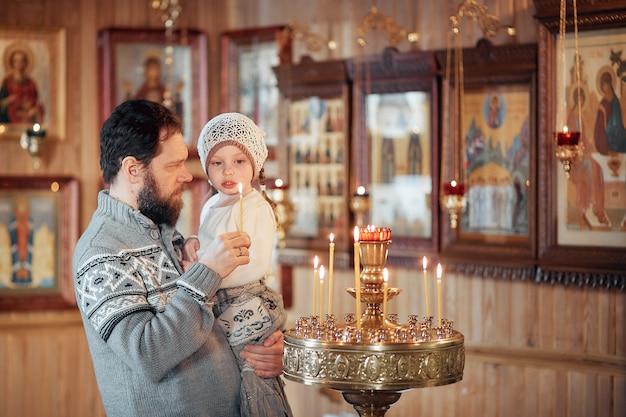 Un homme avec une barbe avec une petite fille dans ses bras se tient devant les icônes et prie dans l'église orthodoxe