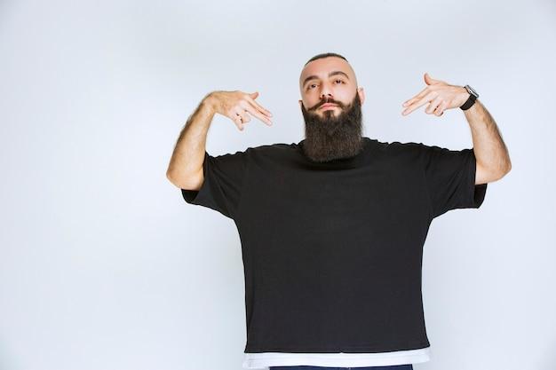Homme à la barbe pointant sur lui-même.