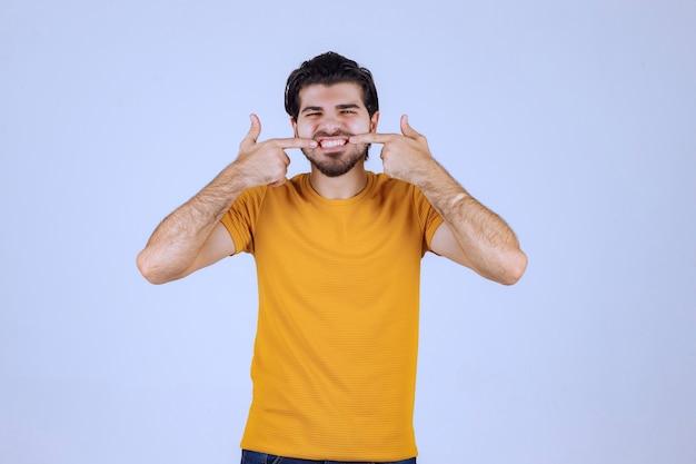 Homme à la barbe pointant vers son sourire
