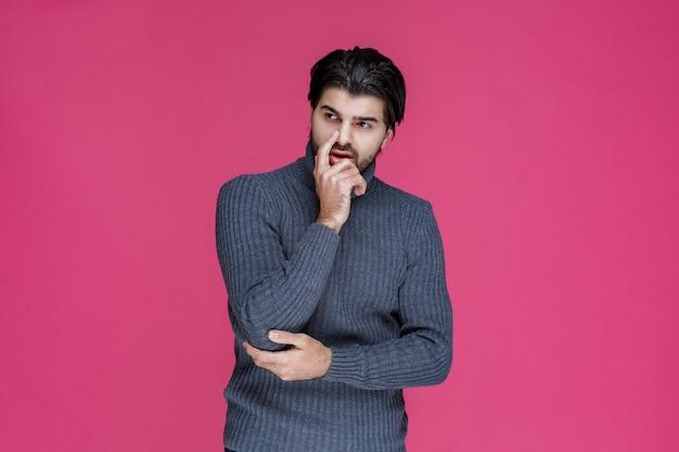 L'homme à la barbe posa sa main sur son menton et réfléchit.