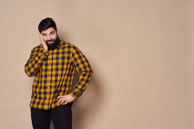 Homme à la barbe posant en studio.