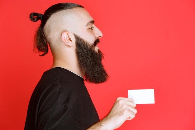 Homme à la barbe présentant sa carte de visite, vue de profil.