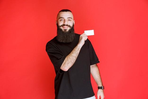 Homme à la barbe présentant sa carte de visite.