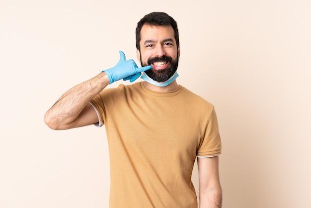 Homme avec barbe protégeant du coronavirus avec un masque et des gants sur un mur isolé faisant un geste de téléphone