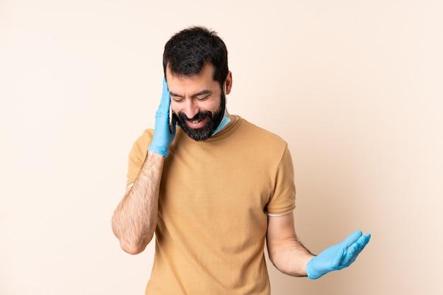 Homme à barbe protégeant du coronavirus avec un masque et des gants sur un mur isolé en gardant une conversation avec le téléphone mobile avec quelqu'un