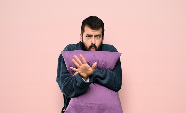 Homme à la barbe en pyjama nerveux s'étendant les mains à l'avant sur fond rose isolé