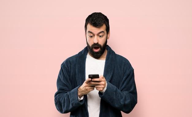 Homme à la barbe en pyjama surpris et envoyant un message sur fond rose isolé