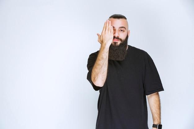 Homme avec barbe regardant à travers ses doigts.