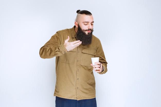 Homme à la barbe sentant son café.