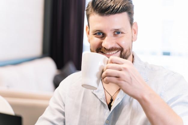 Homme à la barbe souriant tout en tenant une tasse de café