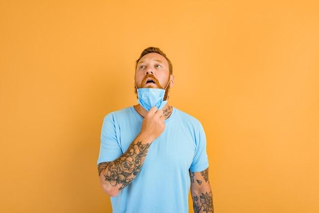 L'homme avec la barbe et les tatouages enlève le masque pour le covid
