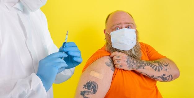 L'homme avec la barbe et les tatouages fait le vaccin contre le covid