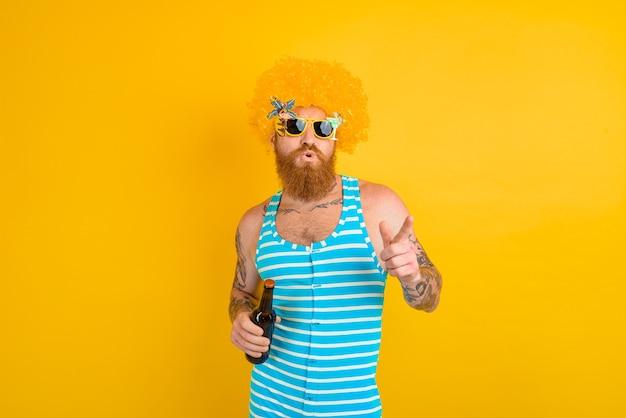 Homme avec barbe, tatouages et lunettes de soleil boit de la bière