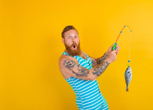 Un homme avec une barbe, des tatouages et un maillot de bain a attrapé un poisson