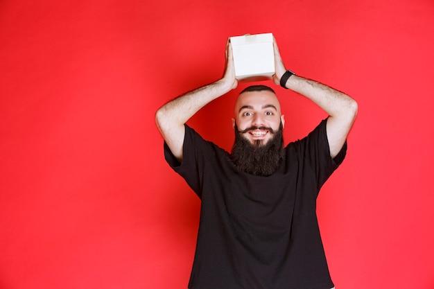 Homme à la barbe tenant une boîte cadeau blanche avec satisfaction.