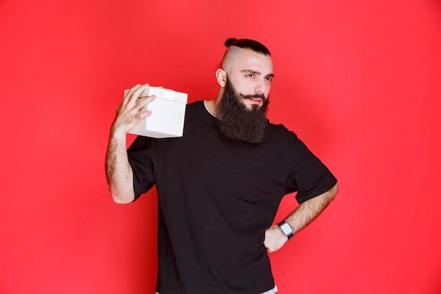 Homme à la barbe tenant une boîte-cadeau blanche et semble douteux de ce qu'il y a à l'intérieur.