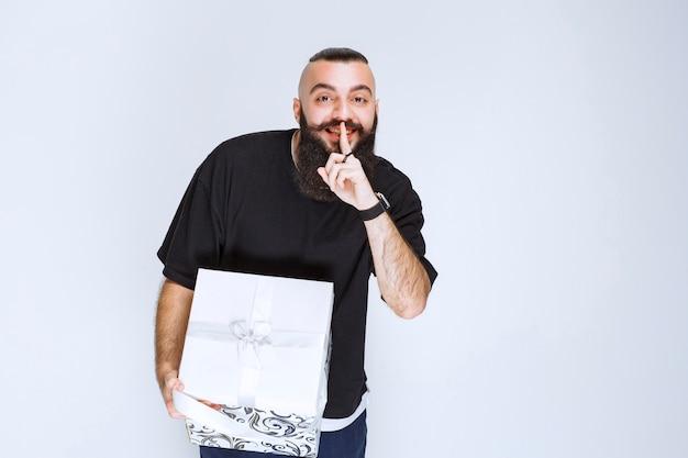 Homme à la barbe tenant une boîte cadeau bleu blanc pointant sa bouche et demandant le silence.