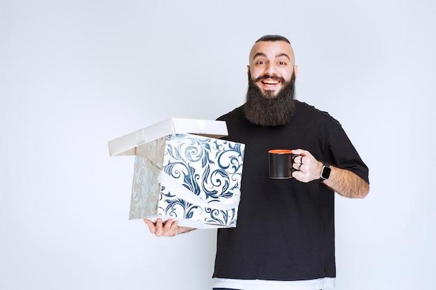 Homme à la barbe tenant une boîte-cadeau bleue ouverte avec une tasse de café et a l'air heureux.