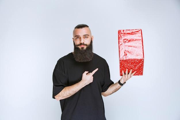 Homme à la barbe tenant une boîte cadeau rouge