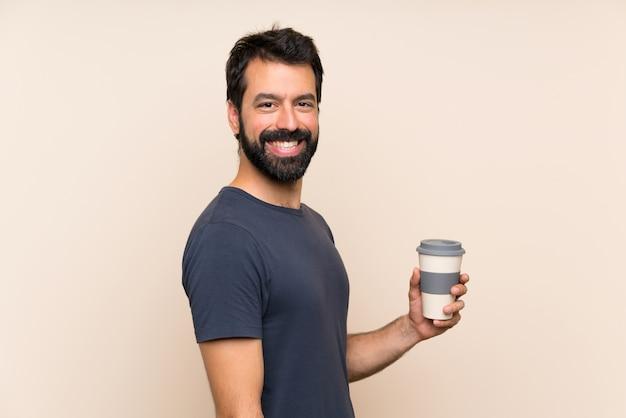 Homme à la barbe tenant un café avec une expression faciale surprise