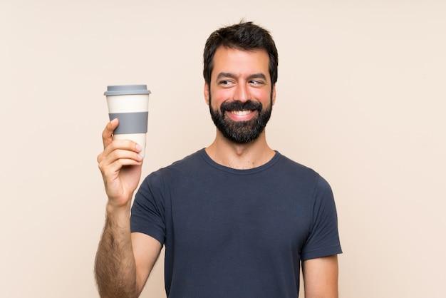 Homme à la barbe tenant un café avec une expression heureuse