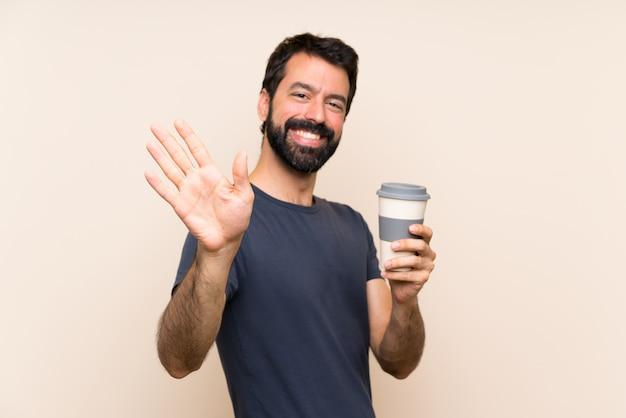 Homme à la barbe tenant un café en saluant à la main avec une expression heureuse