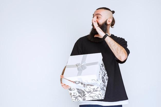 Homme à la barbe tenant un coffret cadeau bleu blanc et appelant quelqu'un.