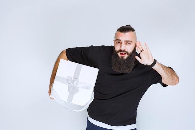 Homme à la barbe tenant un coffret cadeau bleu blanc et écoutant attentivement.